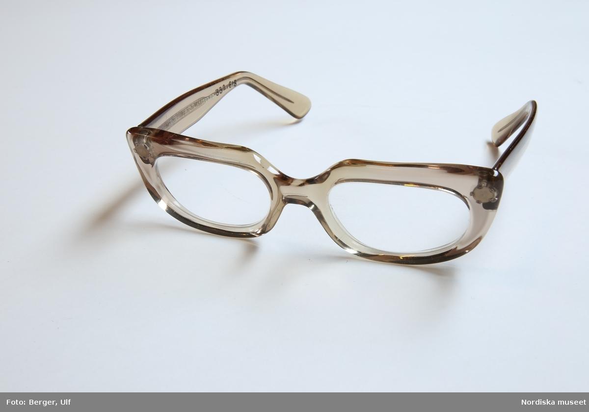 """Ett par glasögon i ljusbrun plast. Rektangulära bågar med rundade hörn. Recept-mineralglas med svagt stärke. Skalmar med böjda ändar. På insidan av vänster skalm står det """"Skaga made in SWEDEN 140"""", på insidan av höger skalm står det """"140 ARTESSE design  C.A. BREGER SID."""". /Petrine Knight, 2014-11-24"""