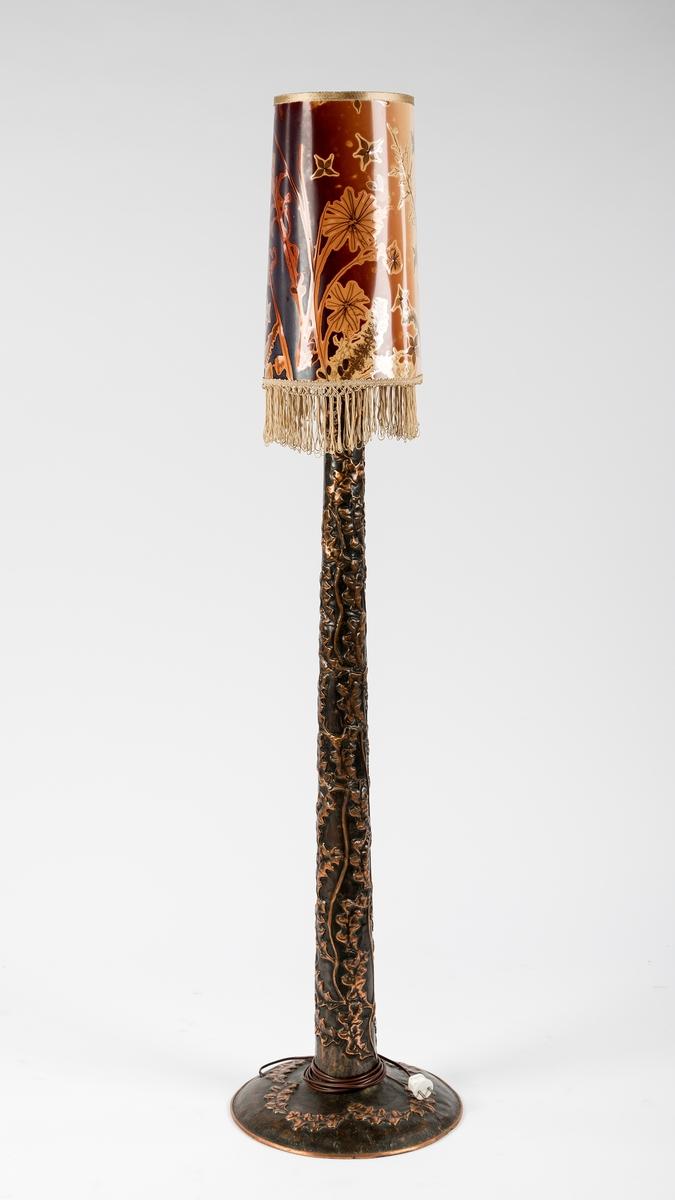 Kopperstett dekorert med bladmønster. Står på rund sokkel. Har pære og ledning.