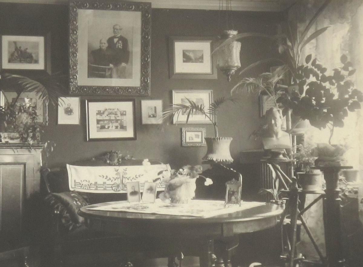 Stuen i Leopold Stockingers hjem. Stue med sofa med hvitt brodert varetrekk i ryggen (= sofa AAM.14844), rundt bord foran med fotografiere og potteplante, på veggen bak mange fotos, øverst pm. ekteparet Stockinger.  Foran vinduet th. potteplanter på blomsterbord, måneskinnslampe, byste av  mann. Tv. piedestall og litt av en stol (14845).