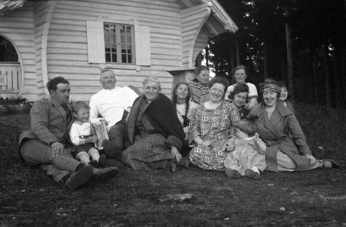 Gruppe mennesker sitter på gresset utenfor Vester-Holm.