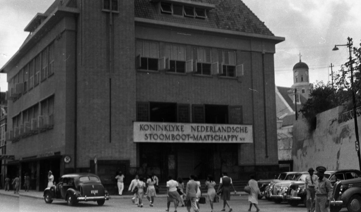 Gateparti i Willemstad. Kjøpesenter med flere biler og personer. Suderøy på vei til fangstfeltet.