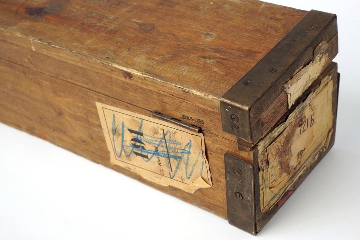Trekasse med låsbart, hengslet lokk. Nøkkel mangler. Kassen er forsterket med metallbeslag. Lokket kan også låses med to påskrudde lærreimer med spenner. Nøkkelhullet er forsterket med metallbeslag.