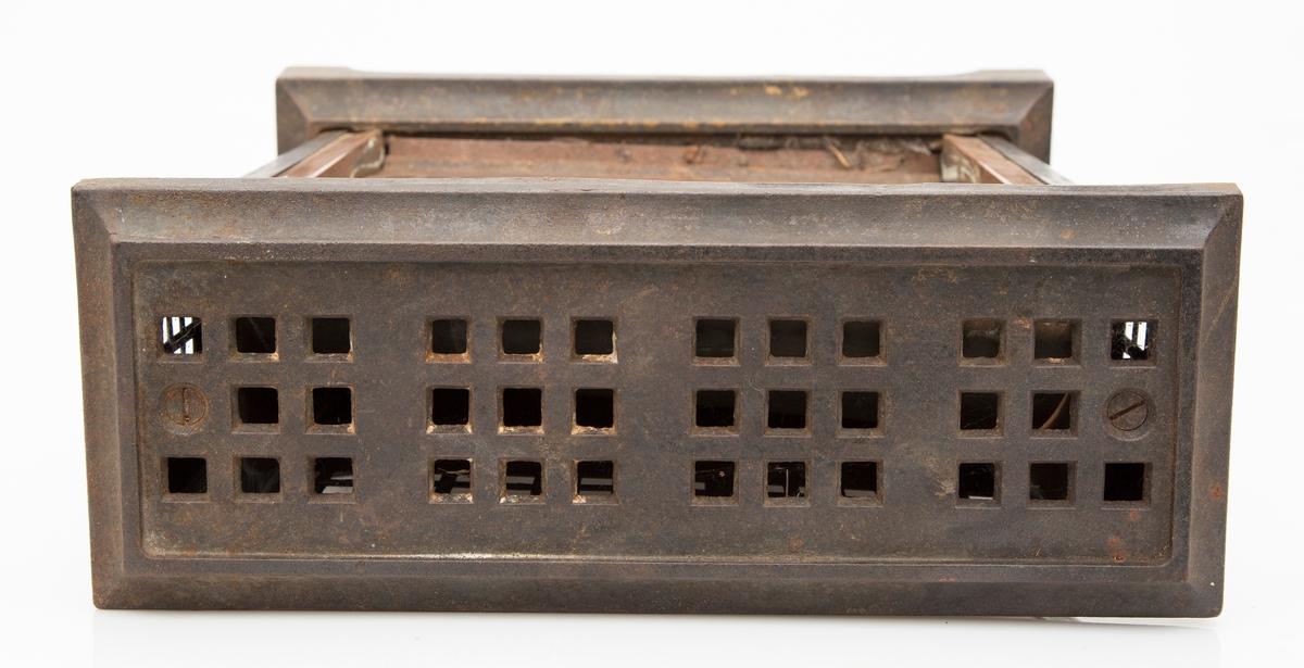 Elektrisk varmeovn i sort jern. Høy, rektangulær modell med stansede luftespalter i toppen, bak og øverst på sidene. Metallrist med luftespalter i front, foran varmeelementet. Sort kabel og støpsel. To brytere på kortsidene.