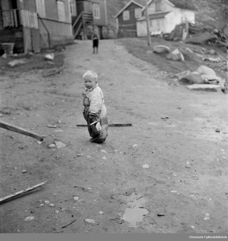 Kjøllefjord 1940. Et ukjent, lite barn med et lekespann i hånden står i en bratt bakke mellom hus i Kjøllefjord. Muligens er bildet tatt i nærheten av Hustadbruket.