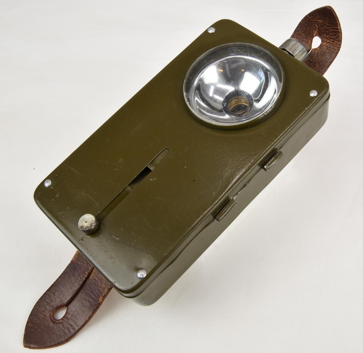 En ficklampa av grönfärgad järnplåt. Ficklampan är av kvadratisk form och är försedd med ett brunfärgat läderband på baksidan med hål för fäste. På lampans övre framsida sitter en lamphållare täckt av ett plant plasthölje. Reglage för avskärmning av belysning sitter på framsidan och regleras med hjälp av en plåt som sitter innanför plasthöljet, som förs upp och ned genom ett metallknopp, över lampan. På lampans övre del sitter en tryckknapp av metall. Lampan öppnas som en ask för att stoppa i eller ta ur batterier. På lampans baksida finns en märkning i form av en sköld krönt av en krona.