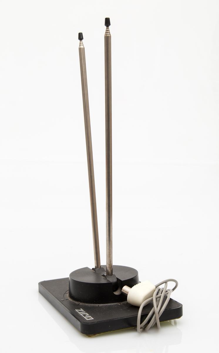 Antenne. Fjernsynsantenne i stål og sort plast. Firkantet plate med 2 teleskopiske antennearmer. Flatpakket i pappeske. Fabrikkprodusert. Mrk. ZICO.
