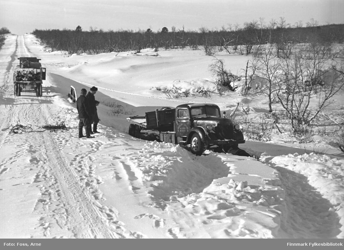 """""""Pohjolan Liikenne"""" lastebil har (antakelig?) kjørt ut av veien i Karigasniemi ved grensen til Norge (i Utsjok kommune i Finland), februar-mars 1947. En annen lastebil har stoppet i veien og er lastet med bygningsmaterialer."""