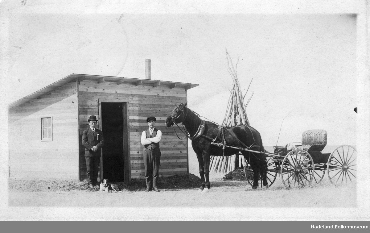 """To menn og hest med vogn foran en hytte. En hund ligger ved bena til mannen til venstre. """"Fra Kopperuds første homestead."""""""