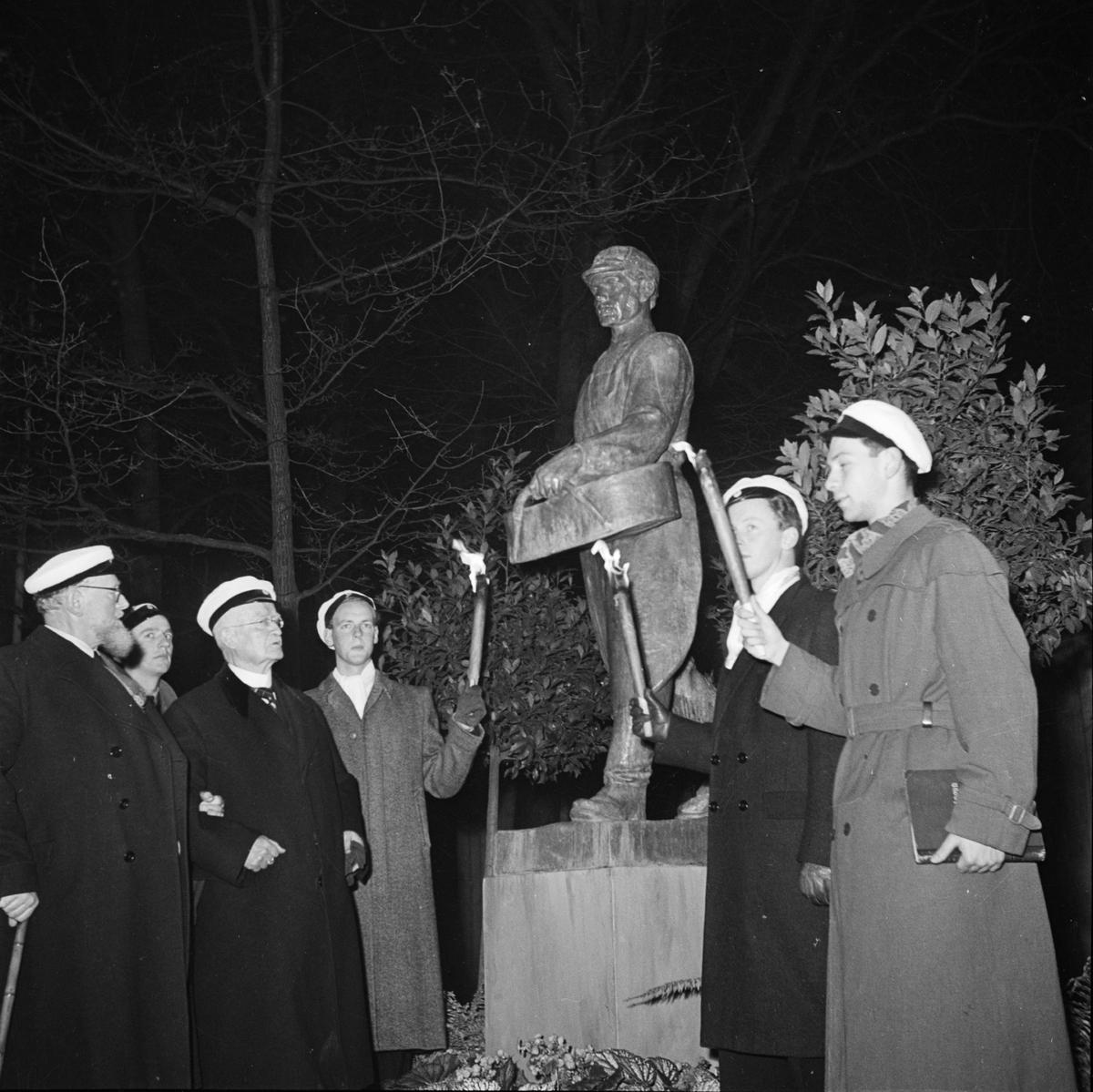 Män med studentmössor och facklor vid avtäckningen av skulpturen Såningsmannen. Längst till vänster skulpturens upphovsman konstnären Gottfrid Larsson. Östgöta nations 300-årsjubileum, Uppsala 1946