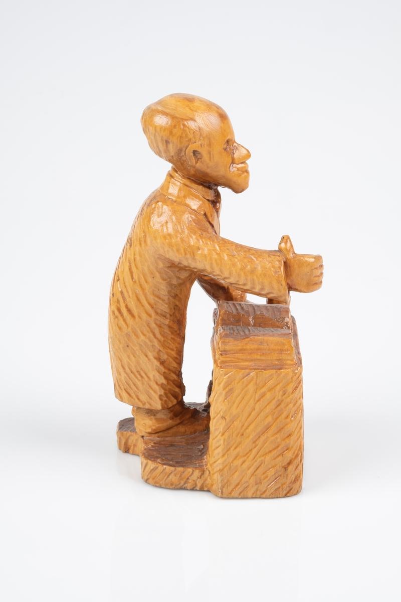 Utskåret trefigur som forestiller en mann på stalerstol. På talerstolen ligger en oppslått bok. Mannen står med den ene armene løftet og viser tommelen opp.