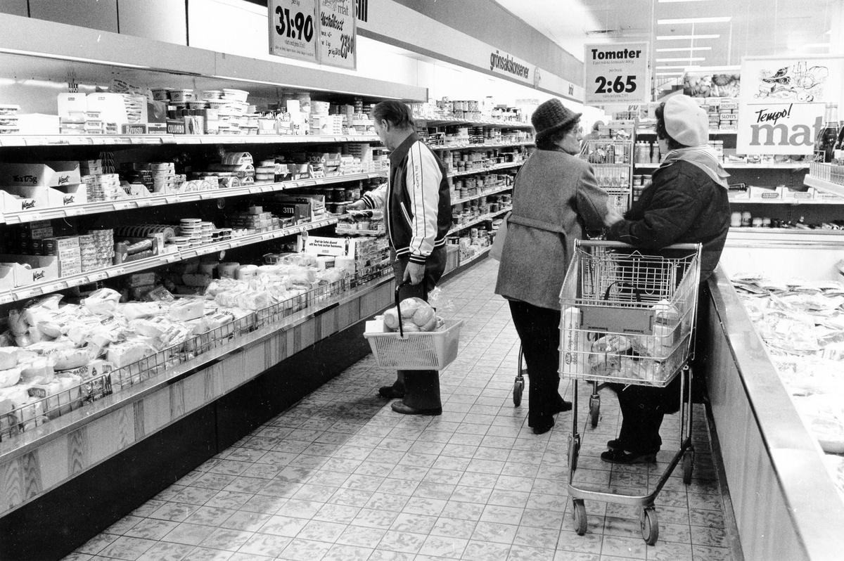 Butiksinteriör med reklamskyltar, hyllor och frysdiskar. 2 kvinnor, med kundvagn, och 1 man, med korg, befinner sig vid frys- och kyldiskarna.