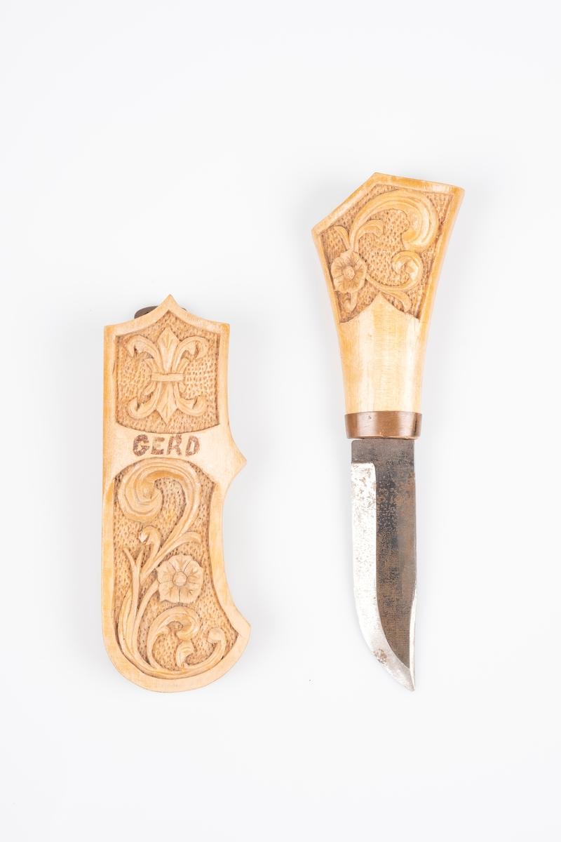 """Tollekniv med slire og skaft i tre og knivblad i jern. Det er utskåret akantusmønster på sliren og skaftet. Navnet """"Gerd"""" er inngravert på framsiden av sliren. På baksiden av sliren er det tekst som trolig er påført i etterkant. Det er en opphengskrok i kobber spikret fast på baksiden av sliren."""