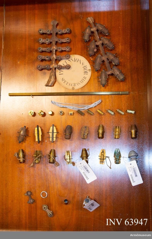 Grupp F II. 31 delar till lätt nedslagsrör m/1864. Till granater till 7 cm framladdningskanon m/1863. Framställt i olika tillverkningsstadier, i monter.