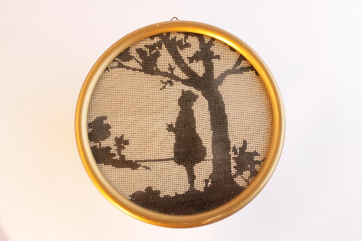 Inramat broderi med guldfärgad träram. Broderat med tekniken petit points. En svart figur mot en ljus bakgrund. En pojke står under ett träd där det sitter en ekorre.
