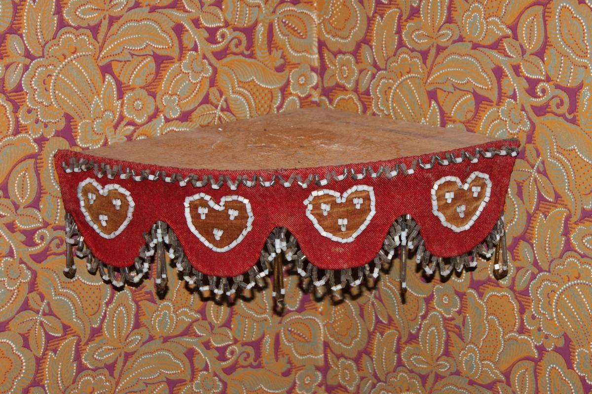 En liten enkel hörnhylla i trä med en fastsatt bård av rött ylletyg med påsydda pärlbroderier med stora glaspärlor. Fyra bruna tyghjärtan som dekorerats runtom och inuti med vita glaspärlor. En kant av glaspärlor upptill samt en frans med hängande pärlor nedtill.