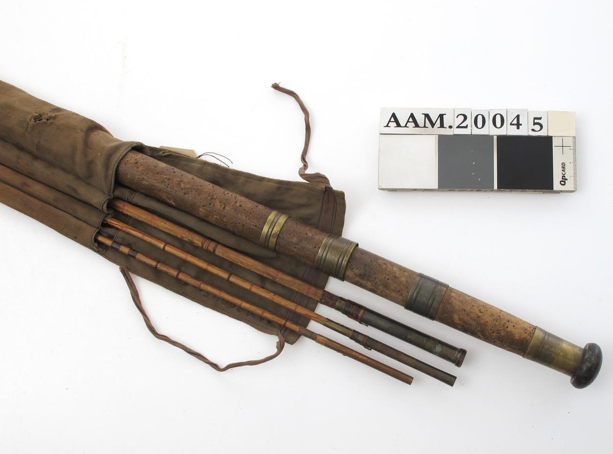 """Fiskestang i lerretspose, 1930 årene.  a) Øvre ledd med håndtak. """"Bambus."""" Langt korkhåndtak beslått med messingringer og toppknott av tre. Stangen er av imitert """"bambus""""', det vil si av løvtre, beiset lysoker og med innskårne ringer i viss avstand, noen med tynn   b) Mellomste ledd. Løvtre, beiset litt mørkere lysoker, ennn treet. Messingrør for feste av neste ledd.   c) Tynnt ledd, sekskantet tverrsnitt, tverrringer med tynn tråd, delvis henger løst. Messingledd.   d) Tynnt ledd, tråder surret rundt 15 cm. avstand  e) Pose. Brunt bommull, lerret med fire rom og""""lokk""""  som kan legges over åpningen, og lukkes med to enderbånd."""