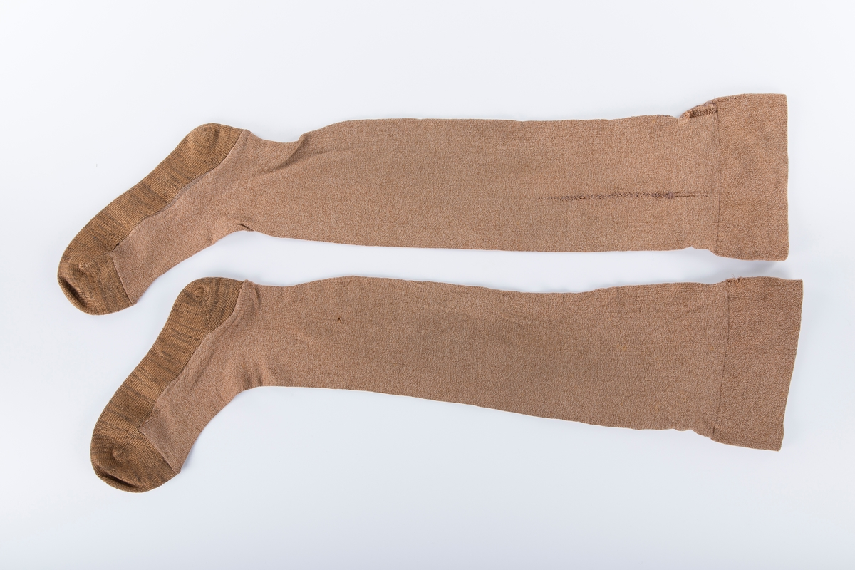Tykke strømper, ett par. Konfeksjon. søm midt bak. Påsatt nystrikket fot under krigen, strikket av Lina Ambjørnrud. Raknede masker stoppet