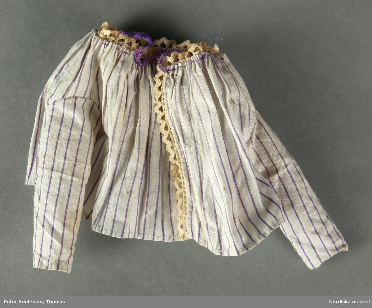 Dockklänning i två delar, bomull, lila ränder på vit botten. a) Långärmad överdel med spetskanter. Bandet av silke som håller ihop överdelen är mycket slitet. b) Kjol med veck och bred linning i midjan. Hör till dockan nm.0333607. /Karin Dern 2019-01-17