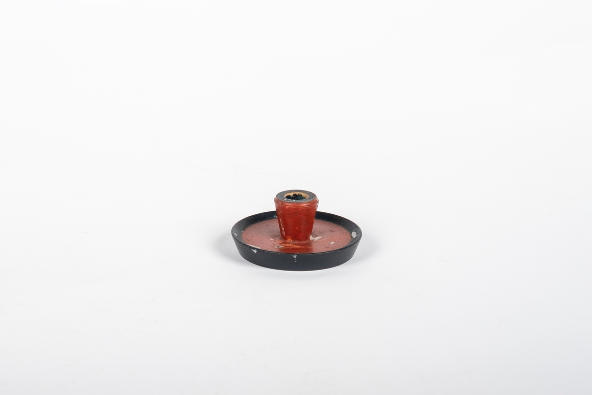 Rund lysestake i tre som er malt rødt og svart. Den har rundt flat skål til fot.