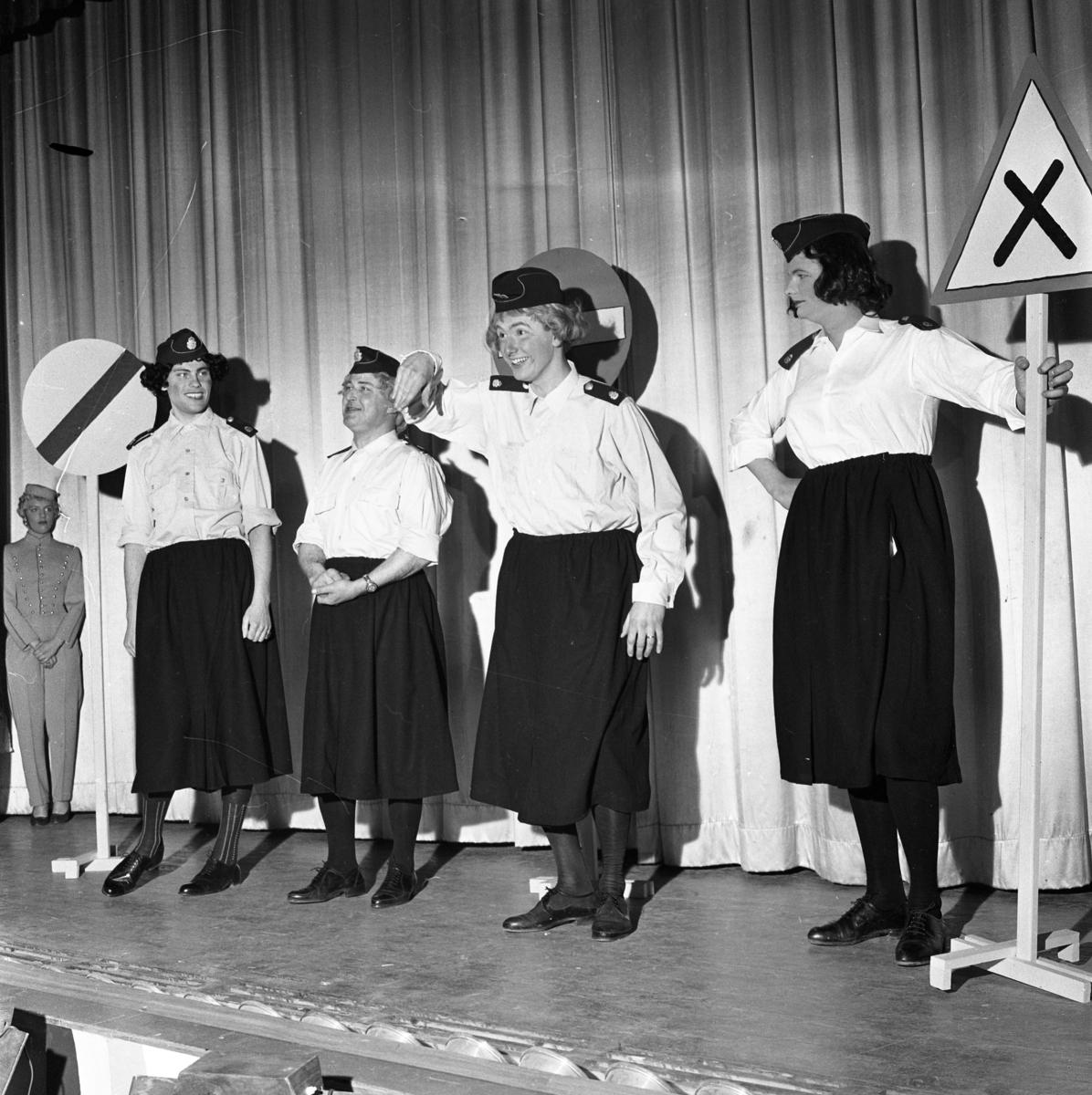 """Årets lokalrevy. En kvinna klädd som piccolo och fyra män utklädda till kvinnor. Från vänster: det kan vara Gullan Kästämä, Benkt Engstrand, Rune Andersson (""""Sotarn), Larz-Thure Ljungdahl och möjligen Mats Torstensson. Trafikmkärken på scenen."""
