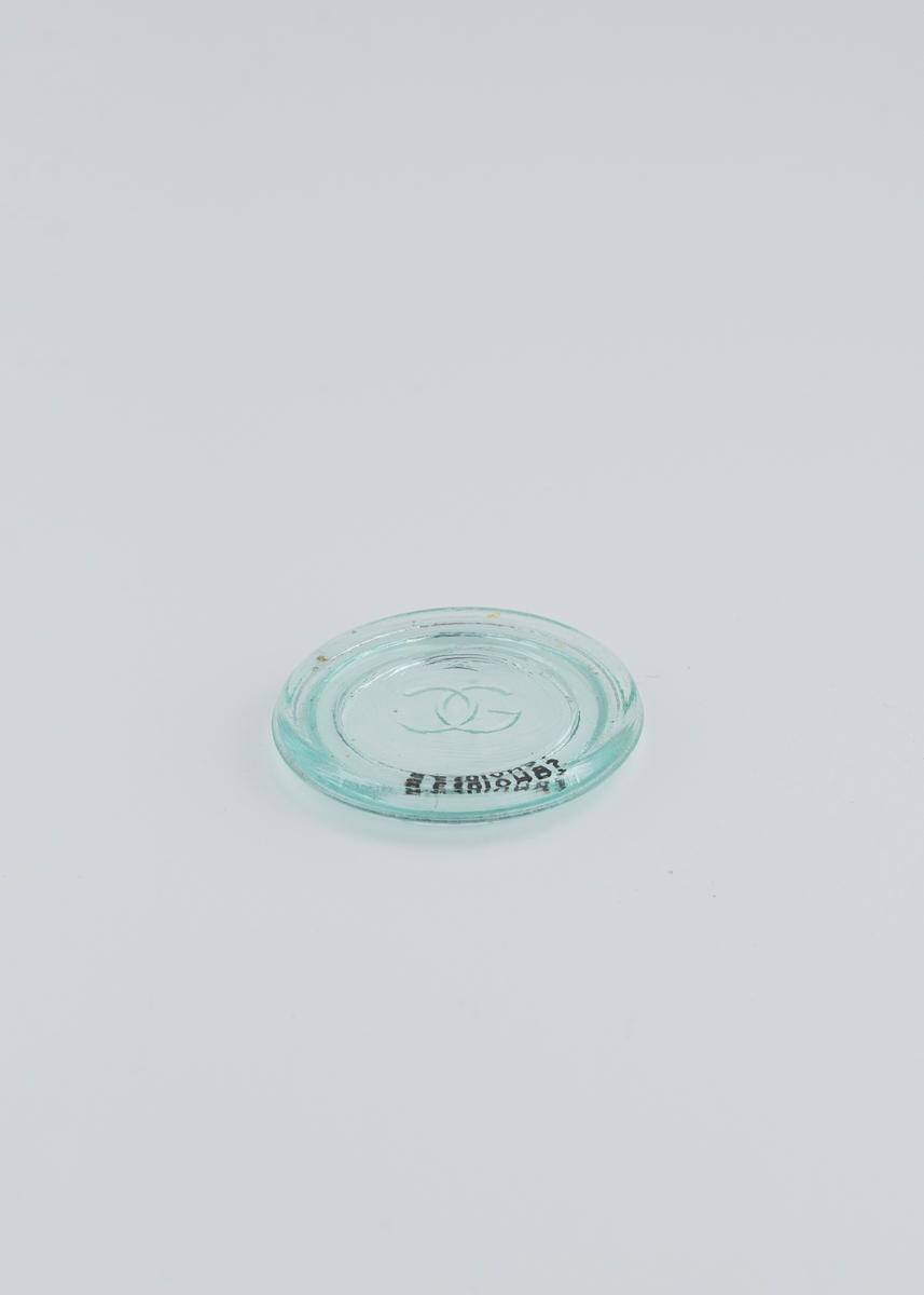 Flatt lite lokk i glass som sitter løst på glasskrukke.