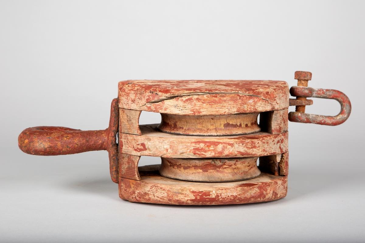 Dobbel blokk med to skiver og krok. Metallfeste i bakkant, muligens for oppheng eller sammenkopling med andre inretninger(?) Rødmalt, som har flassa av.   Alt av trevirke, med unntak av feste bak og krok, som er laget av metall. Skive og bolt i senter er laget av tre.