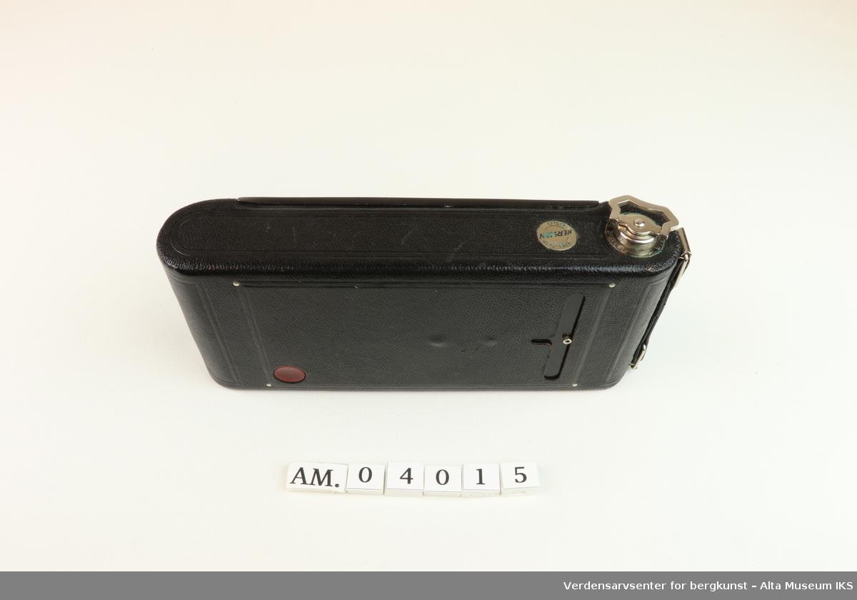 Foldet fotoapparat Diomatic NO. 1A Pocket Kodak. Made in U.S.A by Eastman Kodak Company. Rochester. N.Y. Kodak Anastigmat F 6.3-12.7mm lens NO. 18339. Kamera med rektangulær form og avrundede sider.  På undersiden et hull med gjenger der noe kan skrus inn. På oversiden metalldel med en nøkkellignende utsikker som kan vris rundt. Metallås. Firkantet luke på baksiden for kameralinsen, og rundt rødt vindu til bildetelling. Åpnes ved å dra ned metallås. Kameraet kommer i et brunt lærveske med 530mm lang stropp.