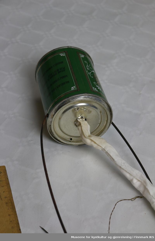 En hjemmelaget parafinlampe med veke, bestående av en parafinholder laget av en gjenbrukt blikkboks, og en sammenrullet blikkboks av samme merke som utgjør røret veken skal tres gjennom. Parafinlampen har håndtak/takfeste laget av bøyde jernstenger.