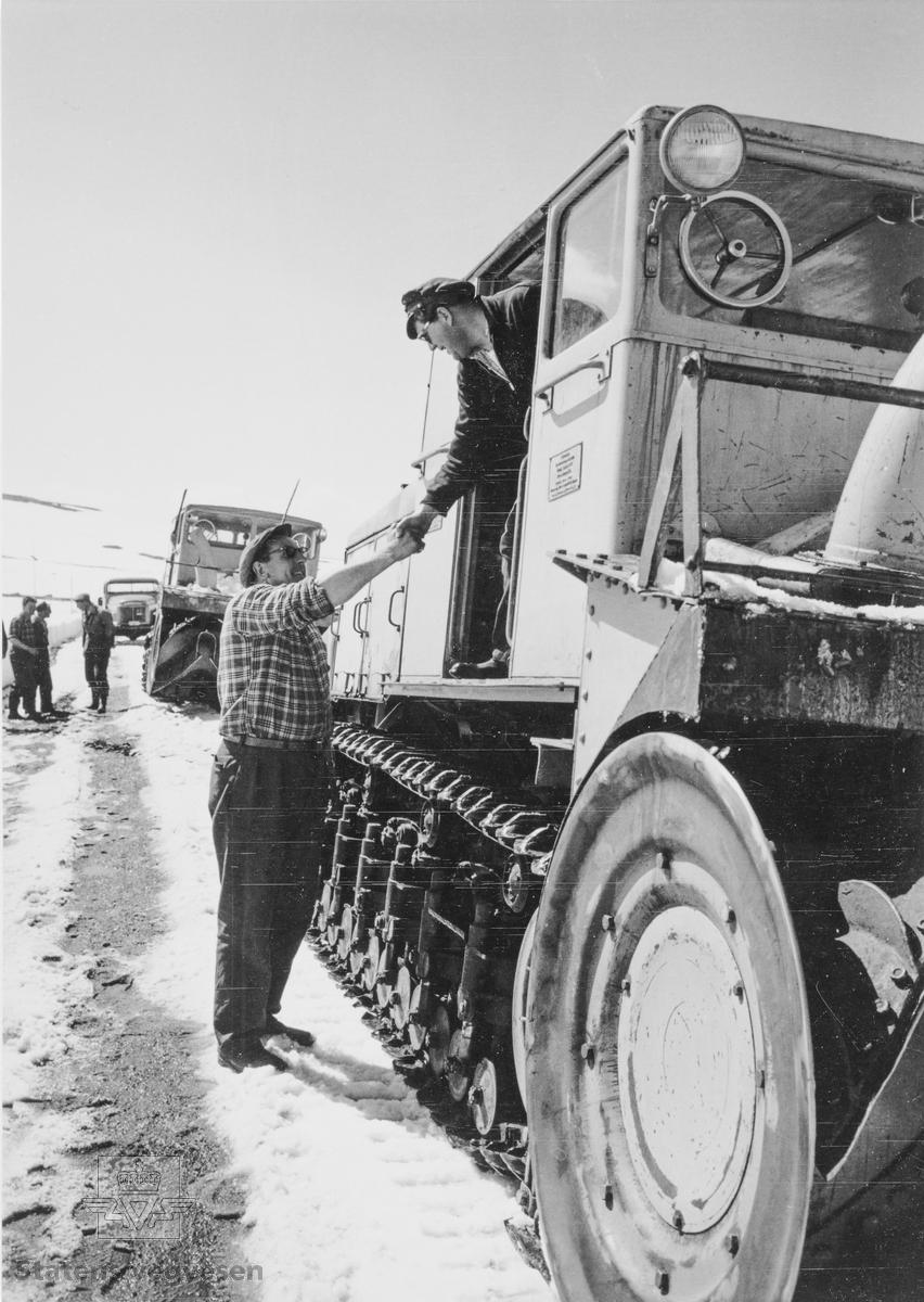 I 1928 ble det åpnet veg over Hardangervidda fra Eidfjord til Haugastøl. Strekningen Geilo-Haugastøl stod ferdig i 1938. Vegen over vidda var vinterstengt fram til 1940. Åpningen skjedde normalt ved St. Hans. Under krigen 1940-1945 brukte tyskerne store ressurser på å holde vegen åpen hele året. Blant annet hadde de et stort antall tunge snøfresere til disposisjon. Etter 1945 ble igjen Hardangervidda vinterstengt i mange år framover. De tyske snøfreserne ble overtatt av Statens vegvesen og brukt vider hver vår ved åpning av Hardangervidda. De gikk gradvis ut av bruk fram til 1980. Den siste har overlevd og er plassert på Norsk vegmuseum Labro.   Her får brøytemannskap fra Buskerud takk for brøytehjelp i Hordaland, trolig fra 1960-åra. Fem personer, to «Peter-freser» og én lastebil i bakgrunnen. I førerhuset sees Henrik Brenden, Statens vegvesen Buskerud.