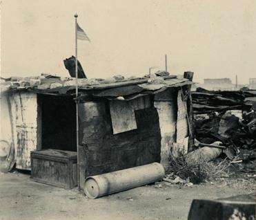 "Boligbrakke i ""Ørken Sur"", Brooklyn NY, ca 1929-1935. Amerikansk flagg heiset på bambusstang ved døren."