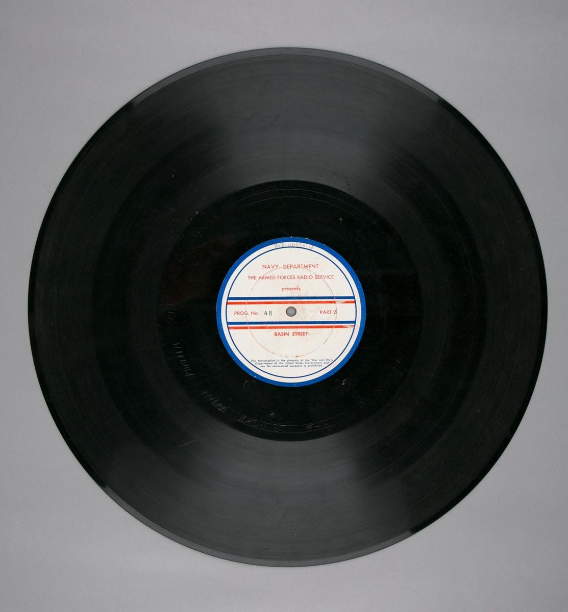"""Grammofonplatesamling. LP-plate med tittel """"The Armed Forces Radio Service"""" utgitt av Navy Department. Plate i svart vinyl spilles på platespiller med 33 1/3 omdreininger i minuttet (33-plate)."""