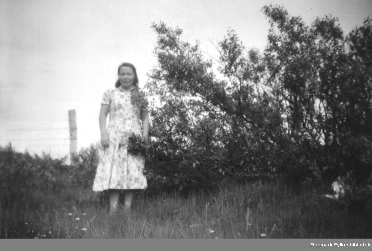 En kvinne fotografert på et jorde. Person og sted er ukjent, men det kan være i Nesseby kommune.