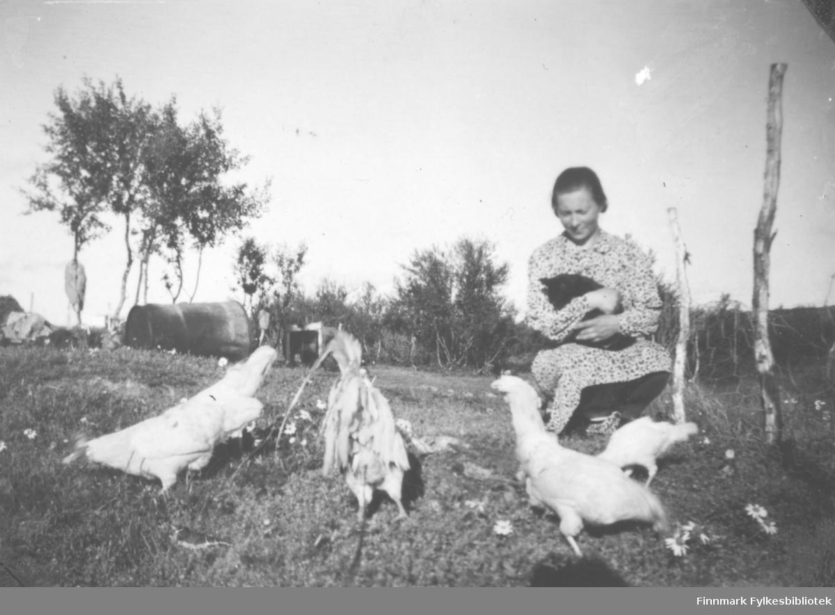 Bigga Mathisen sitter på et jorde ved småbruket deres i Oterbekken i Nesseby kommune.