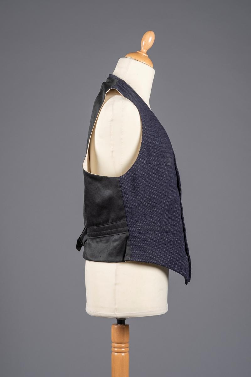 Vest med forstykke i mørk blått ullstoff og bakstykke i mørk blått silke. Den har foring i stripemønstret bomullsstoff. Det er spensel i ryggen og den lukkes i front med seks knapper. Vesten har fire forlommer og en innerlomme.