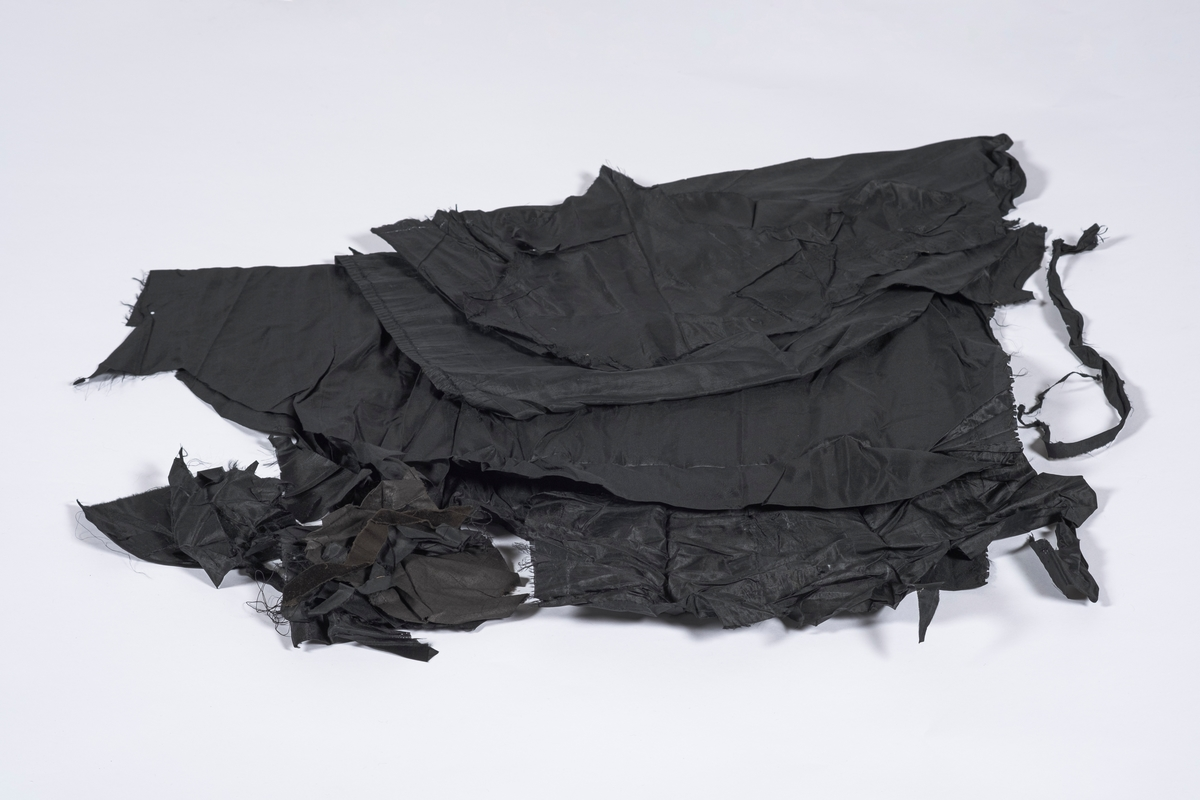 Tøyrester fra todelt brudekjole bestående av kjoleliv og skjørt. I alt 31 biter av varierende størrelse. 5 av bitene er større, resten er smått.