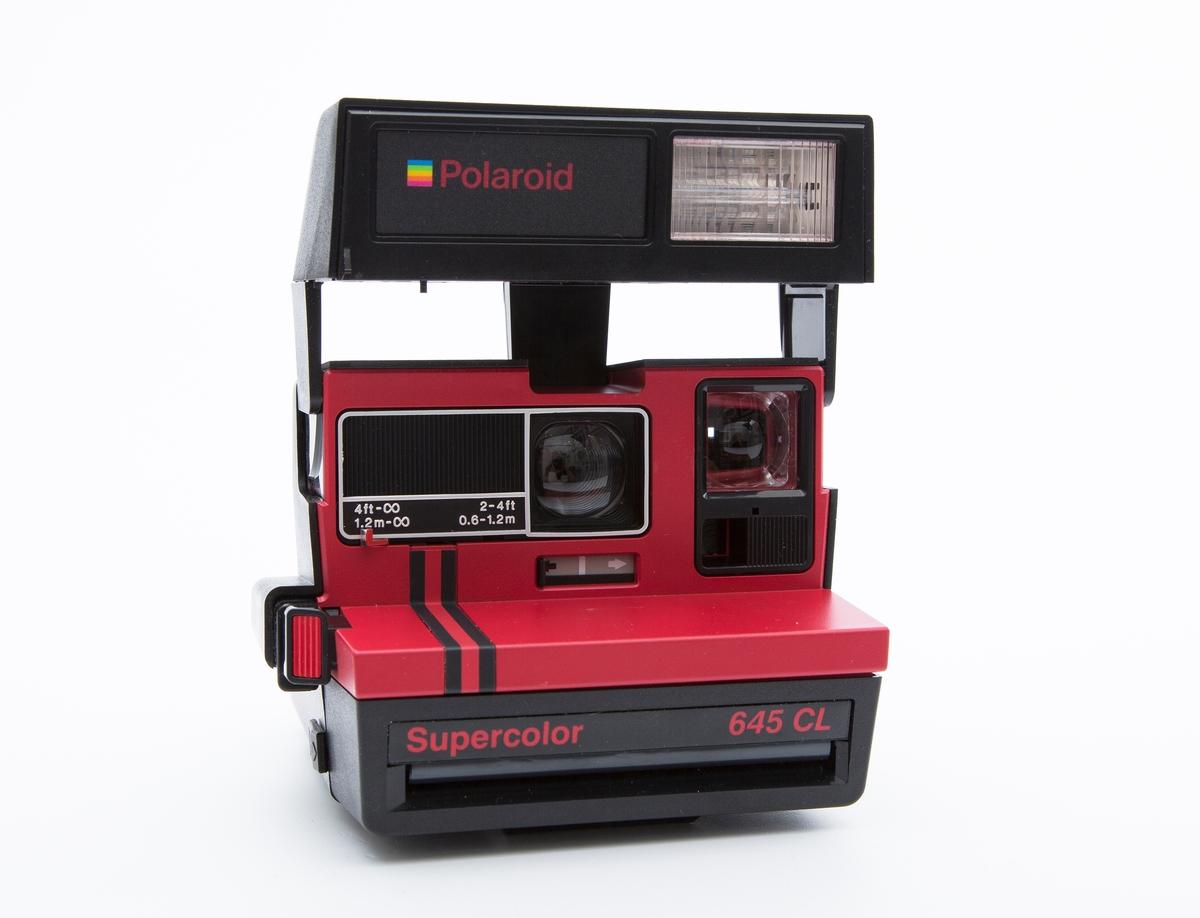 """Kamera i plastikk, svart og rødt. """"bokseformet"""" med toppblitz innebygget. Flat front. Fabrikkprodusert.Merket: Polaroid.Kamera er av den typen der bildet blir fremkalt påstedet.Er i originalembalasjen med instruksjonsheftet."""