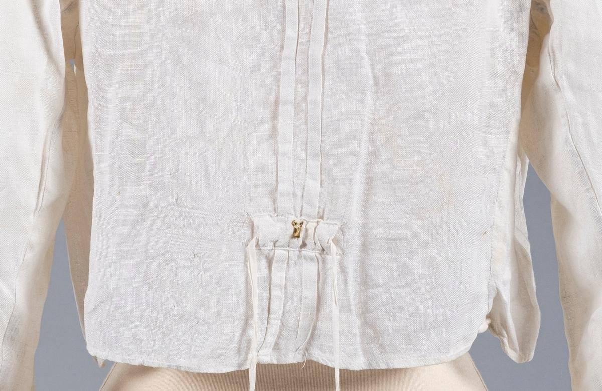 Hvit kjoleliv av lin med blomsterbroderi. Den har puffermer og høy hals. Mansjettene og halsen er forsterket med bomull. Det er sydd folder/brett over skuldrene og ved åpningen. Kjolelivet lukkes med knapper kledd med tekstil. Det er en klaff som skjuler disse knappene. På klaffen er det påsydd pynteknapper av perlemor. Mansjettene lukkes med to perlemorsknapper. Halsen lukkes med trykknapper. På baksiden er det påsydd snor trolig for snøring. Ved snoren er den en metallhekte.