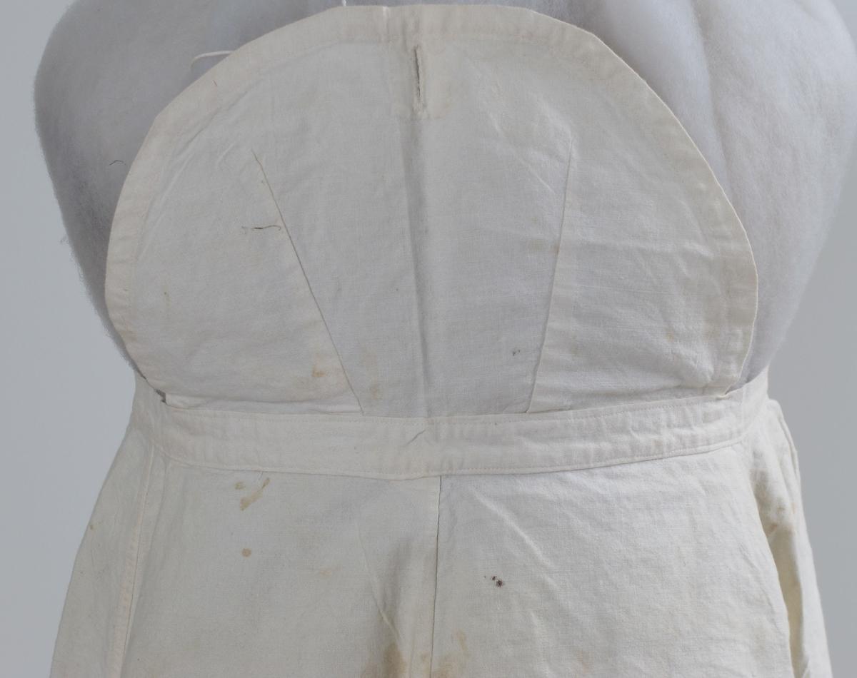 Stort arbeidsforkle av hvit bomullslerret. Maskinsydd. Knapphull øverst for feste i bluseknapp.