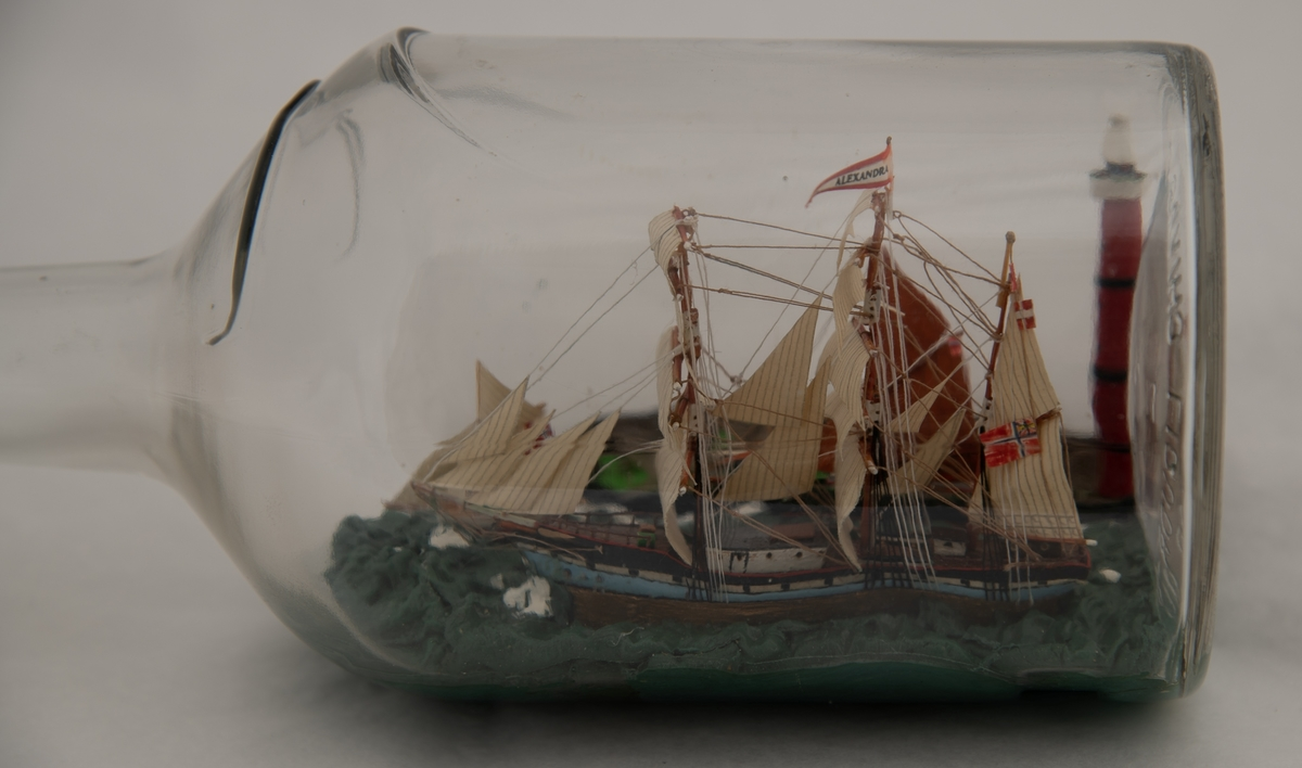 """Flaskeskute: Bark """"Alexander"""" med fyrtårn , losbåt og jakt.  Flaske i klart , svakt blålig glass , knop av seilgarn og om munningen , rød lakk. Profillinje øverst og på halsen , etikettmarkering.  På styrbord side av barken en sort jakt med røde seil , forut en losbåt. I hjørnet ved bunnen et rødt fyrtårn."""