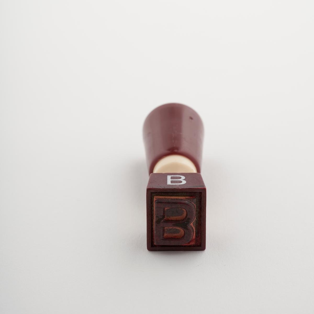 Stempel. Når man presser stempelet på papir lager det et merke med bokstaven B.  Stempelet ble brukt for å vise at et brev skulle sendes med B-post.  NAV-samlingen er en gruppe av gjenstander som har vært anvendt på sosialkontoret (Aetat - NAV) i Skedsmo kommune.