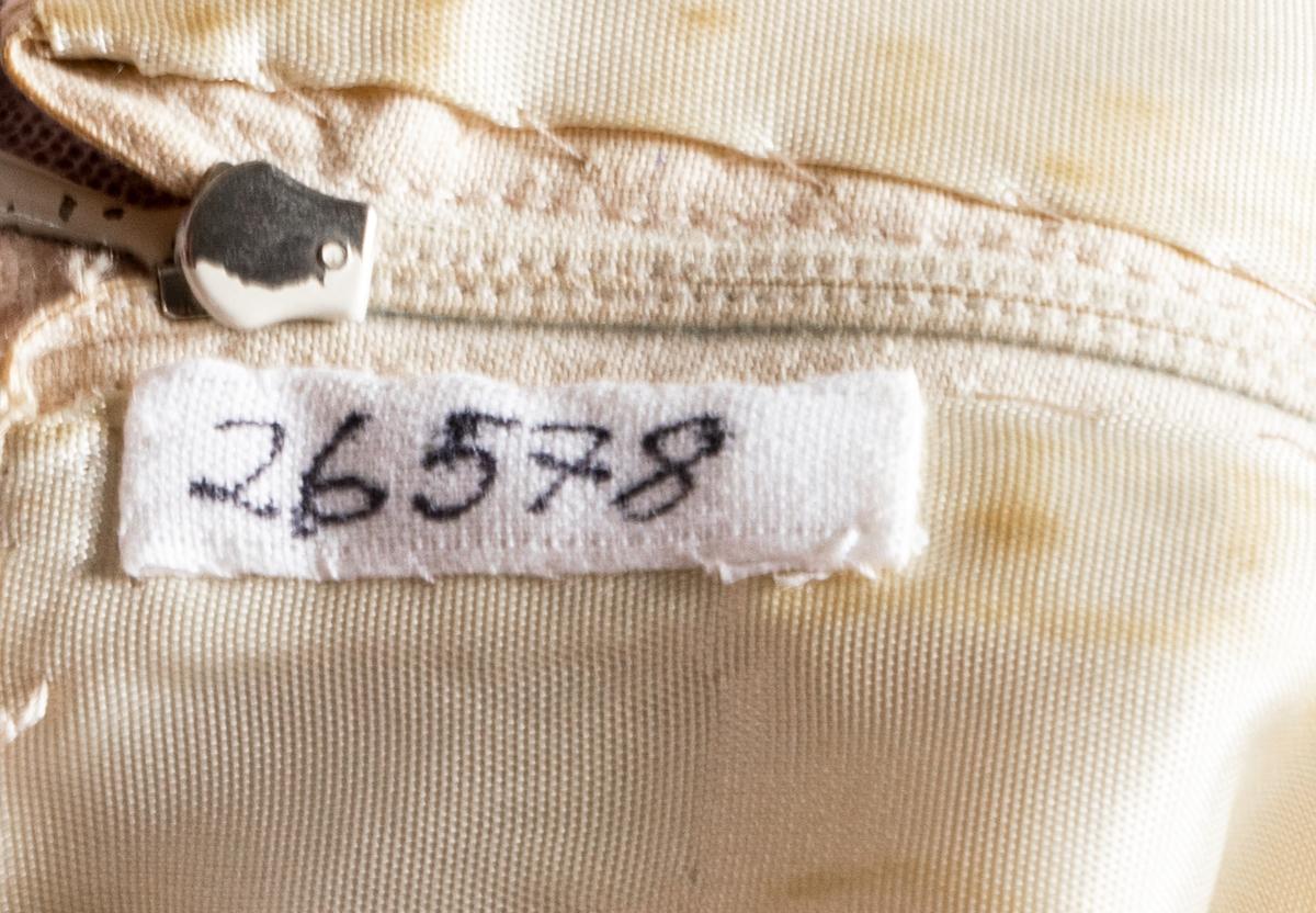 Ärmlös klännig i gulvitt tunt tuskafaftvävt ylletyg. 5 st passpoaler infällda från bysthöjd ner till fållen. De 2 nerdersta med rosetter mitt fram. Dragkedja bak + hyska och hake. Fodrad med gul taft.