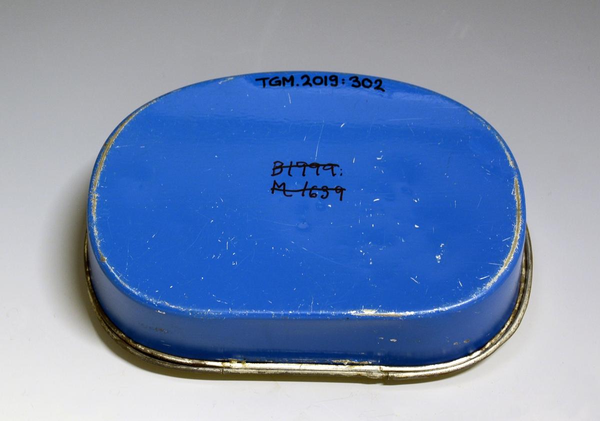 Matboks av blikk med hengslet lokk. Selve boksen er mørk blå, lokket flerfaget med motiv fra et kalsserom med fire elever og en lærer kledd i blått som peker med pekestokk på en tavle. Oppi boksen ligger lenker i plast.