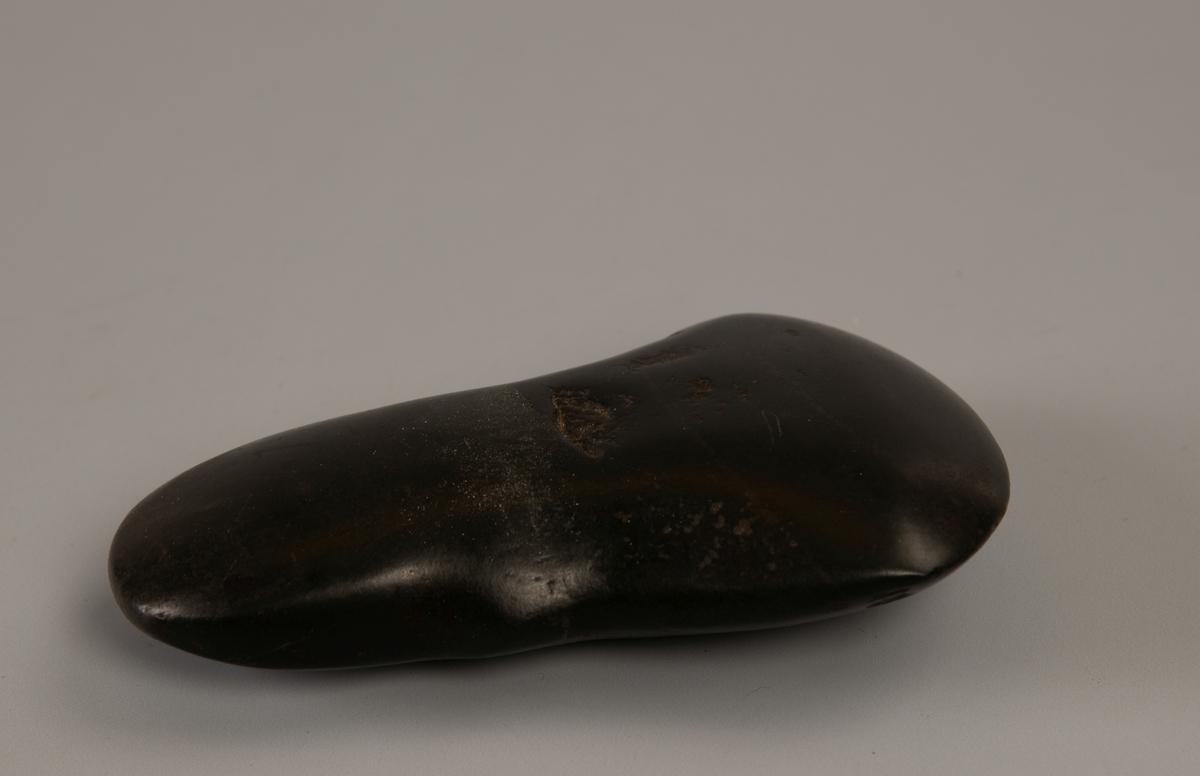 Glatt, blank stein som er svakt hvelvet på begge sider, rundet i den ene side, utskrånende kanter mot den fint rundede, halvrunde egg.