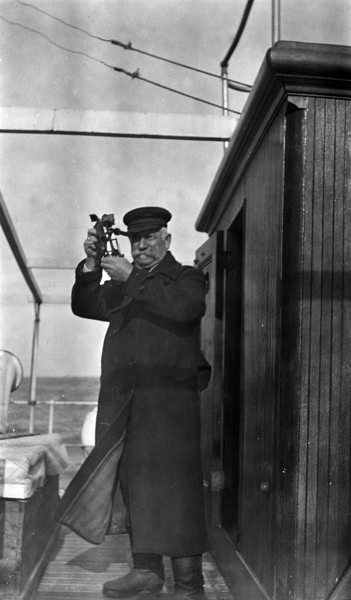 Kaptein Gustav Waage tar ut kursen med en sekstant, ombord på D/S STORFOND.