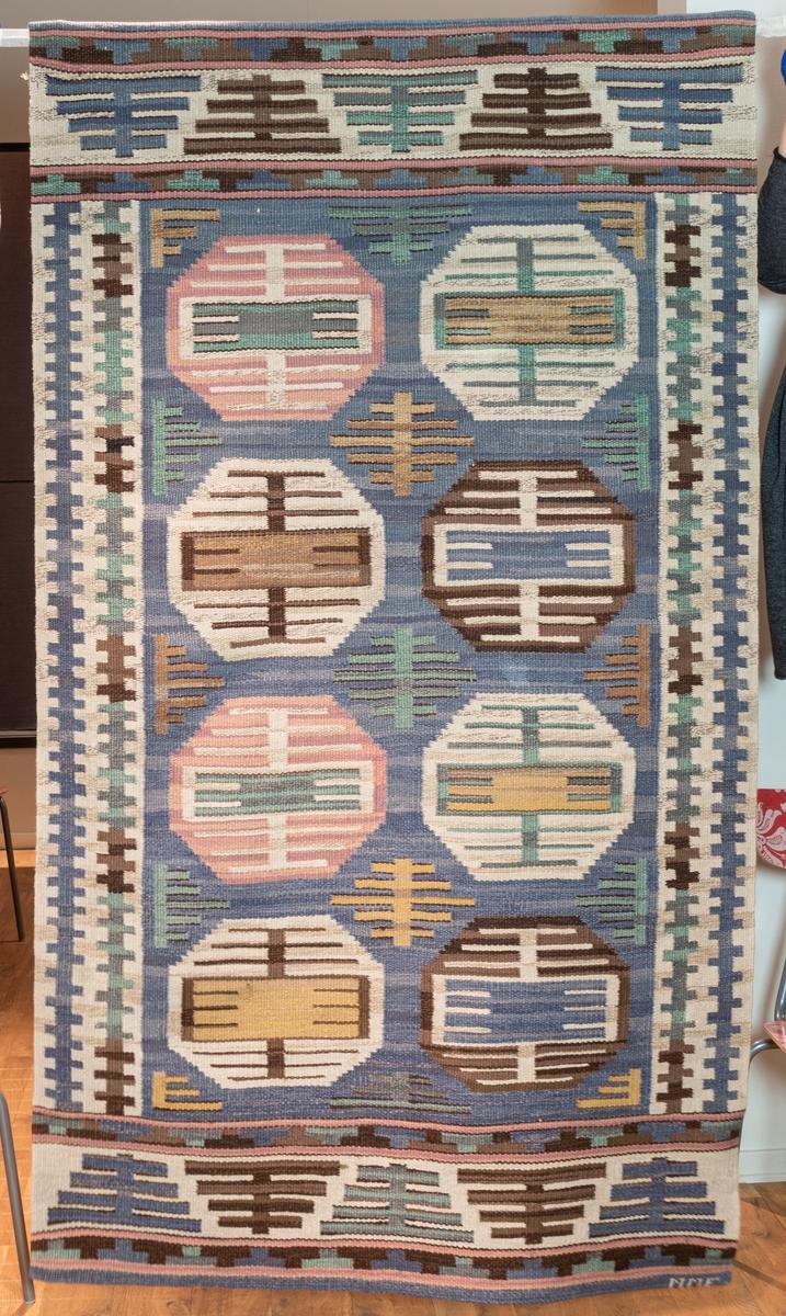 """Matta, Röllakan, 191 x 112. """"Dukater"""". Varp av blångarn. Blå, insprängd botten i mittfältet, vita insprängda bottnar i bårderna. Mönstringen i rosa, grönt, gult i bleka toner samt brunt. Flätad frans. Sign. M. M. F. 1924. Äldre katalogisering av Elisabeth Thorman (enl. uppgift).  Längd: 191 cm          Bredd: 112 cm Varp: 3 tr/cm            Inslag: 8/cm Varp gulgrått, oblekt lingarn, inslag ljusgrått, grått, ljusrött, ljust blårött, grönblått, gröngult, gulbrunt, beiget, flera nyanser av blått och brunt djurhårsgarn troligen 1 tr, röllakan. Jämnt fördelade över mittpartiet, 8 st 8-kanter med geometriskt mönster inuti, runt omkring geometriska figurer, botten i flera nyanser blått, längs stadkanterna 2 tandade längsgående ränder, botten ljusgrå, vid kortsidorna en bred tvärbård av geometriska figurer mot en ljusgrå botten, därom en bård av t-former, på var sida om t-bården tvårränder i ljusrött, ytterst en blå tvärrand. Vid båda kortsidorna avslutas väven med en vikning och ett ca 2,5 cm tygstycke i ljusblått och grågult, troligen lingarn, dräll, är fastsydd för hand över vikningen.  Vid ena hörnet invävd signatur MMF i ljusgrått djurhårsgarn.  Ca 8 cm från ena kortsidan är mattan trasig i båda stadkanterna.  Ett ca 13 cm brett vitt tygstycke i linne, tuskaft, fastsydd på avigsidan längs ena kortsidan.  Komponerad av Märta Måås-Fjetterström 1924.  Se Lundgren: Märta Måås-Fjetterström och vävverkstaden i Båstad 1968, sid 112.  Ulla-Britta Sandström april 1980  Foto Nordiska museet: 388 Q.f. (se katalogkort)."""