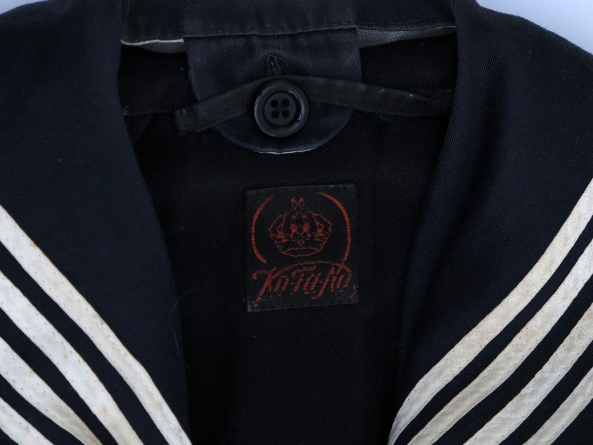 Matroskjole, foldeskjørtet er festet med knapper til overdelen. Mørk blå farge, med hvitstripet matroskrage og hvite striper nederst på hvert erme. Røde vinkler og rød stjerne på venstre erme. Etikett i nakken.