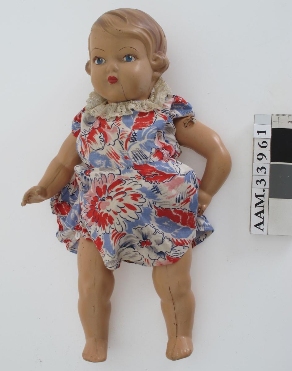 Plastdukke, alle deler støpt i plast, hode og kropp i ett.  Kledd i kjole av blomstret bommulstøy. Armer og ben var festet med strikk gjennom kroppen.  Reparert med ny strikk og knapp på yttersiden av benet.