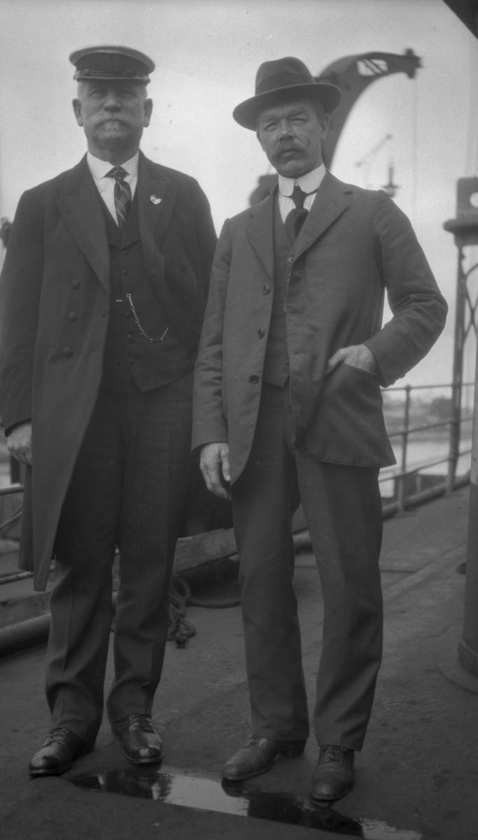 To menn i dress ombord på D/S STORFOND, kaptein Waage til venstre.