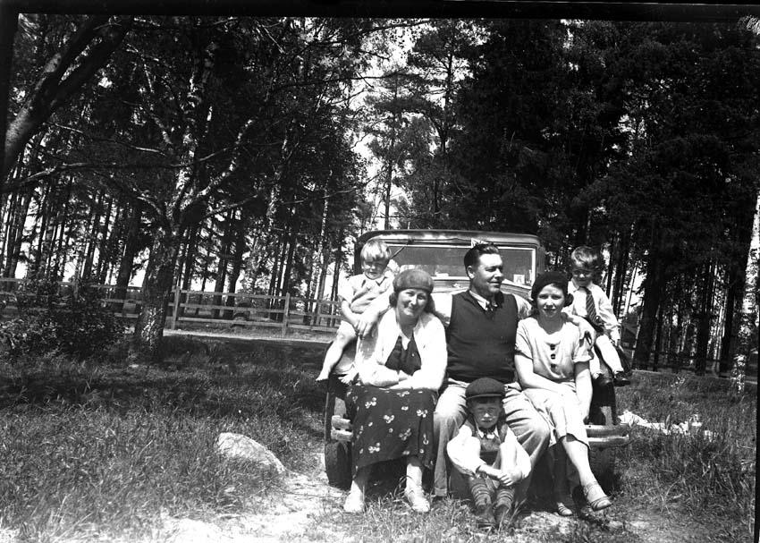 Gruppfoto av personer sittande vid och på en Volvo.