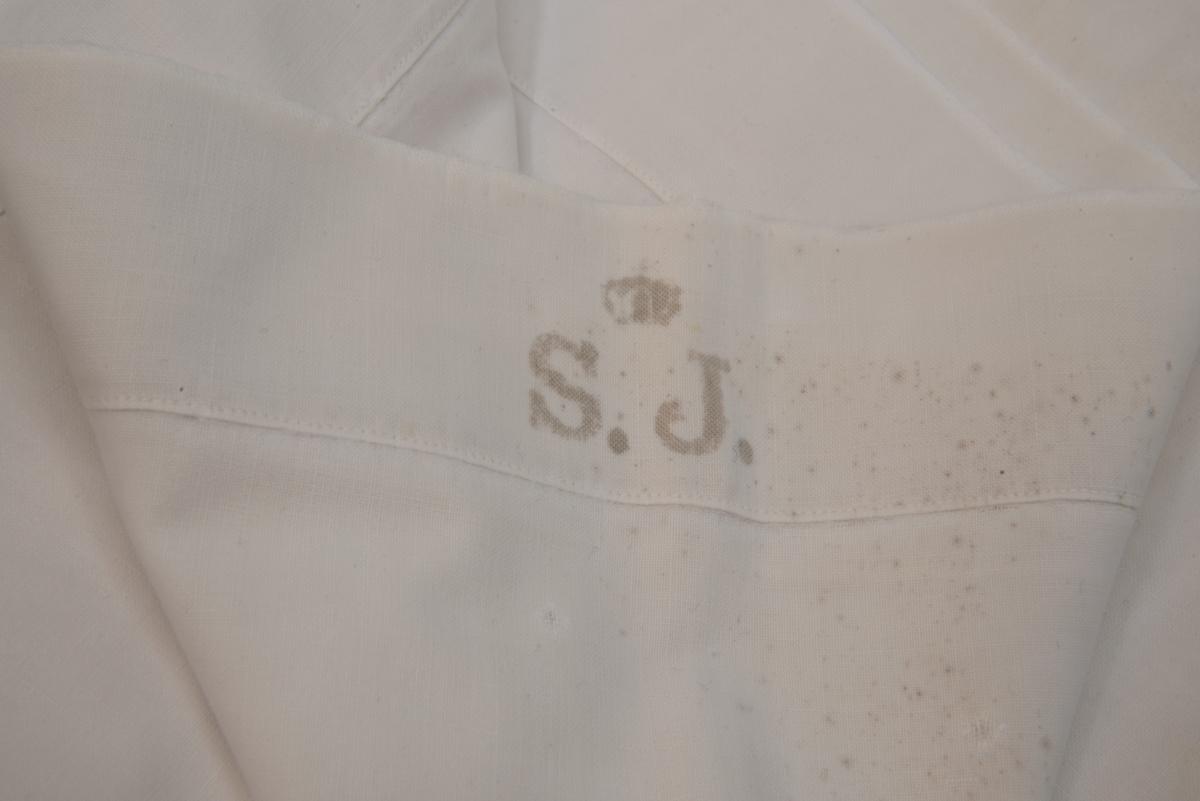 """Påslakan, vitt med tryck """"S.J."""" krönt av en kunglig krona. Påslakanet har flera lagningar."""
